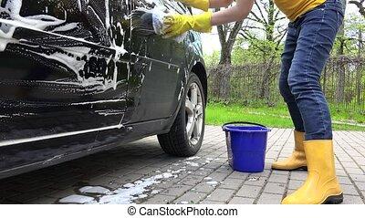 Woman washing automobile in open air. Handheld shot. - Woman...