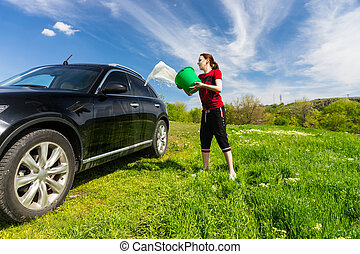 Woman Washing Car with Bucket of Water in Field