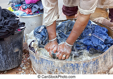 Woman washing cloths by hand in the Draa Valley, Morocco.