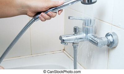 Woman washing detergent suds off bathroom water sink while...