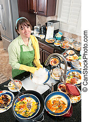 A homemaker washing a bunch of dirty, filthy dishes in a domestic kitchen.