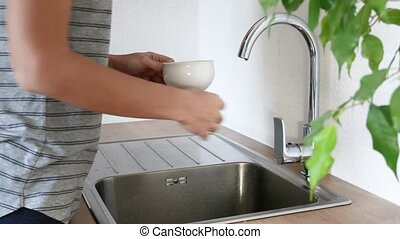 Woman washing dishes in the sink