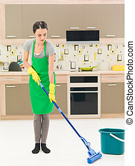 woman washing floor with mop