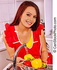 Woman washing fruit at kitchen.