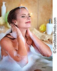 Woman washing hair in bubble bath.