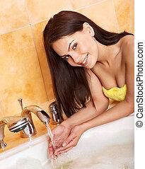 Woman washing hand in bath.