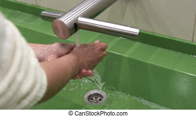 Woman washing hands in restroom