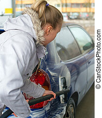 Woman washing her car at the car wash.