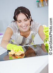 woman washing kitchen with green gloves