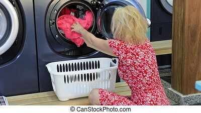 Woman washing machine - A blonde caucasian maid woman...