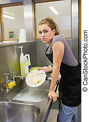Woman washing the dishes in the kitchen