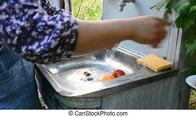 Woman washing tomatoes at washstand outdoors
