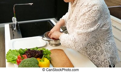 Woman Washing Vegetables In The Colander