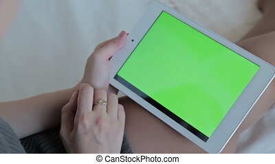 Woman watch on green screen tablet computer closeup. The concept of buying Christmas gifts via the Internet.