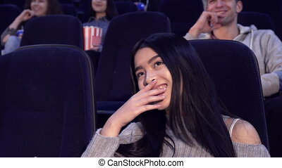 Woman watches comedy at the movie theater - Attractive asian...