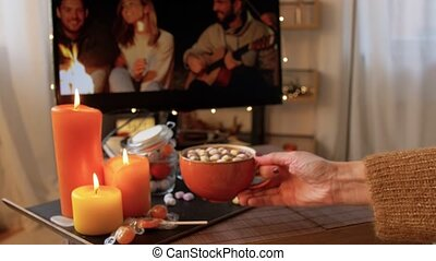 halloween, holidays and leisure concept - young woman watching tv and drinking hot chocolate with marshmallow with her feet on table at cozy home