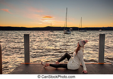 Woman watching a cool winter sunset from the jetty