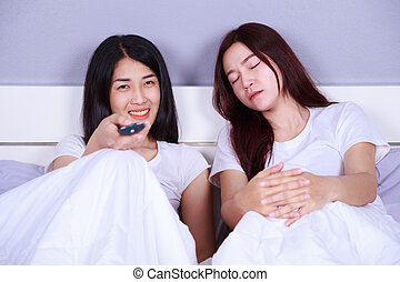woman watching a television while her friend is sleeping on bed
