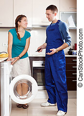 Woman  watching as worker repairing washing machine in her home