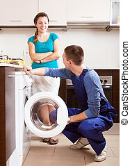 Woman watching as young  worker repairing washing machine