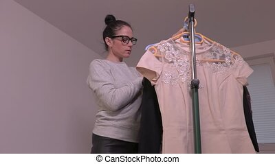 Woman watching blouse near the rack