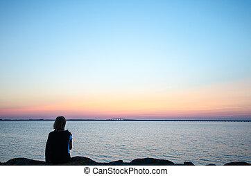 Woman watching bridge at sunset