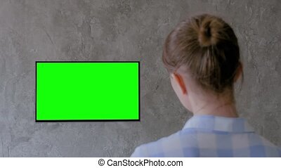 Woman watching flat smart led TV with blank green display hanging on wall in grey living room at home. Green screen, mock up, copyspace, leisure time, template, entertainment and technology concept