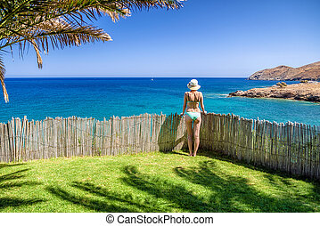Woman watching from garden on the sea