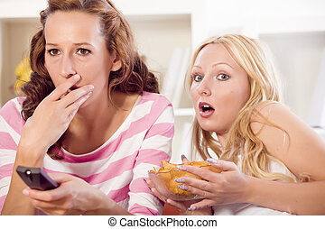 woman watching horror movie - two women watching horror...