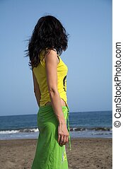 woman watching ocean - side view of a woman watching the ...