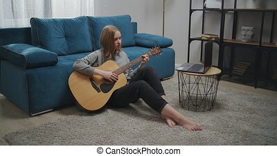 Woman watching online lesson while sitting on the floor in the room. Girl learns to play the guitar on isolation. An aspiring musician learns to play a musical instrument using a laptop. Overhead shot. High quality 4k footage
