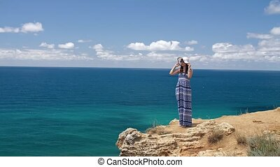 Woman watching seascape - Woman wearing dress and hat at the...