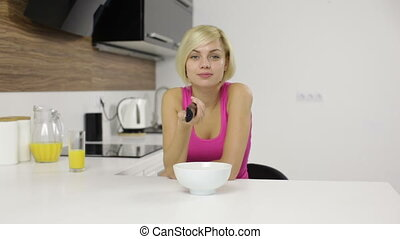 woman watching serious interesting tv hold remote control eat corn flakes, girl changing channels modern kitchen home