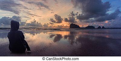 woman watching sun on the beach