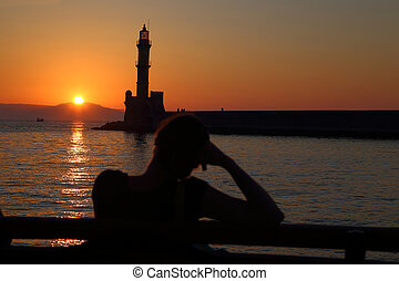 Woman watching sunset behind the lighthouse Chania Crete