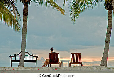woman watching sunset from beach in Kota Kinabalu, sabah,...