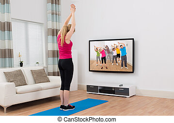 Woman Watching Television And Exercising At Home