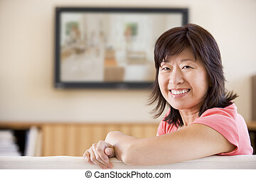 Woman watching television smiling