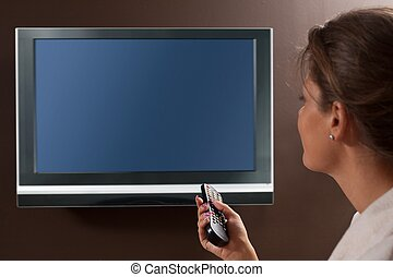 Woman watching television - Woman in living room watching...