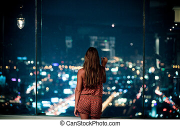 Woman watching the city at night