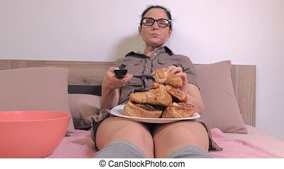 Woman watching Tv and eating junk food