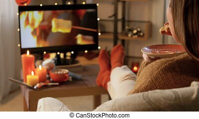 halloween, holidays and leisure concept - young woman watching tv and eating waffle at cozy home