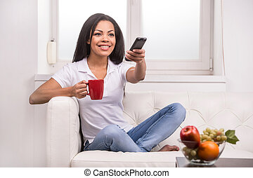 Woman watching tv at home and holding a remote control. Smiling woman on couch changing TV programme