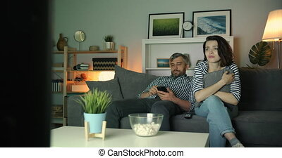Woman watching TV crying while guy using smartphone at home...