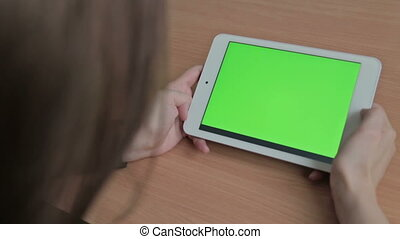 Woman watching videos on tablet, green screen