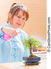 Woman watering bonsai tree