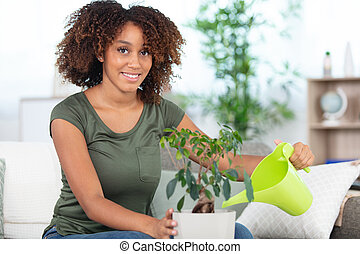 woman watering flowers at home