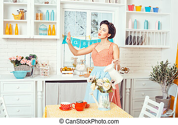 Woman watering flowers. - Pin-up style. Woman in an apron in...
