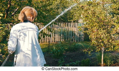 Woman watering from a hose a plant in her own garden