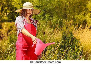 woman watering plants in garden